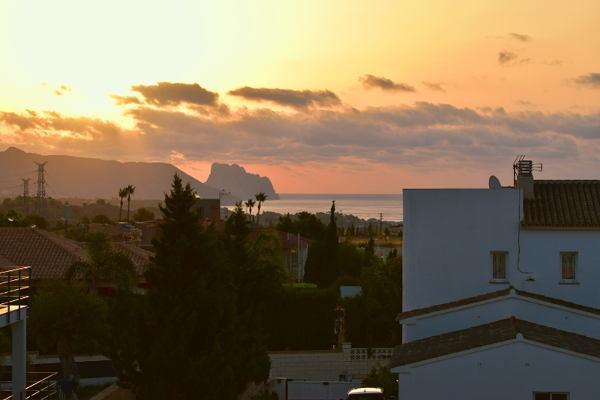 geel, roze, rode lucht met huizen en de rots van Calpe, vakantievilla