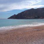 geel zand, stromende blauwe zee, wit schuim en grote rots, Albir