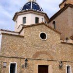 Kerk, bestaande uit lichtbruine stenen, donkerbruine deur en blauw koepeltje.
