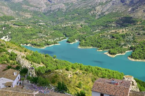 blauw stuwmeer, groene naaldbomen, huizen, Guadalest, de bergen in