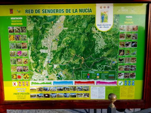 Een houten bord met daarin een poster. Op de poster staat een kaartje met 4 gekleurde wandelroutes. De poster is groen en geel van kleur.