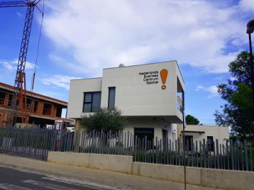 Wit gebouw, zwarte letters, oranje uitroepteken, hoog hek, hier wordt Nederlandse les gegeven.