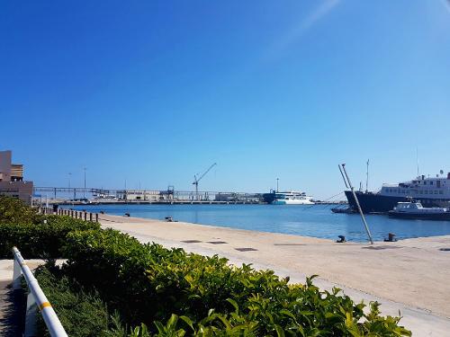 Blauwe lucht, zee, kade, boten en een groene heg, Denia