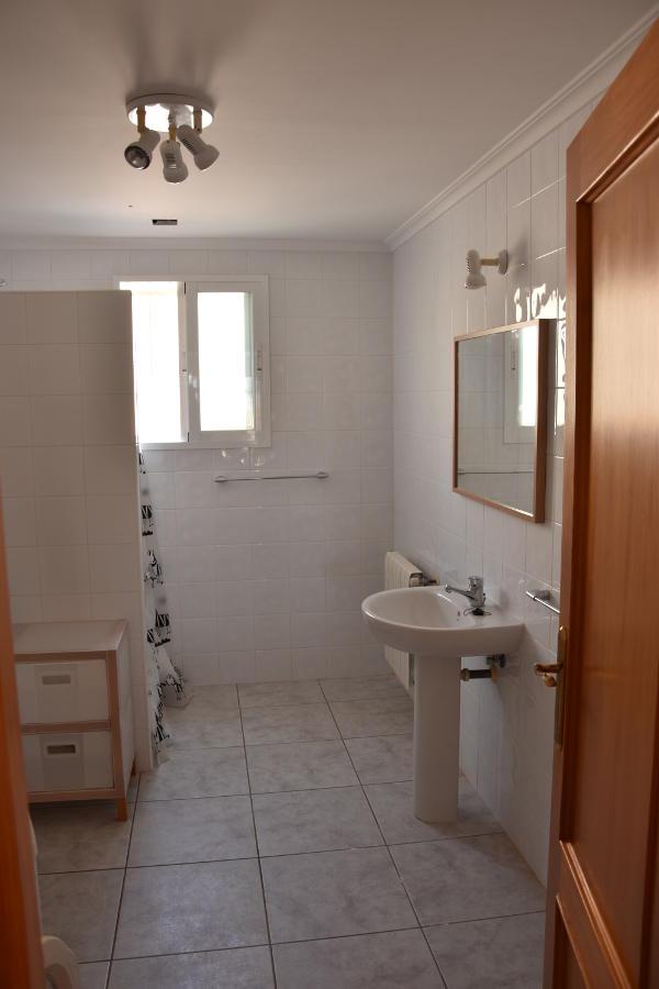 Een douche, witte tegels aan de muur, grijswitte vloertegels, een wastafel met spiegel, vakantiewoning