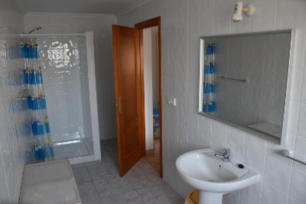 Witte tegels, douche met blauw douchegordijn, wastafel en spiegel; vakantiewoning