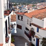Een straatje met trapje, witte huizen, oranje daken met op de achtergrond een berg.