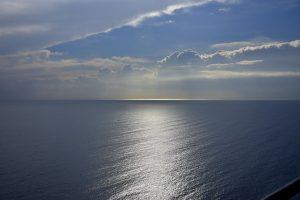 Heel veel water, blauwe zee, zonnestralen, blauwe lucht met wolken
