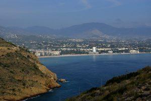 Blauwe lucht, blauwe zee, rotsen en een strand.