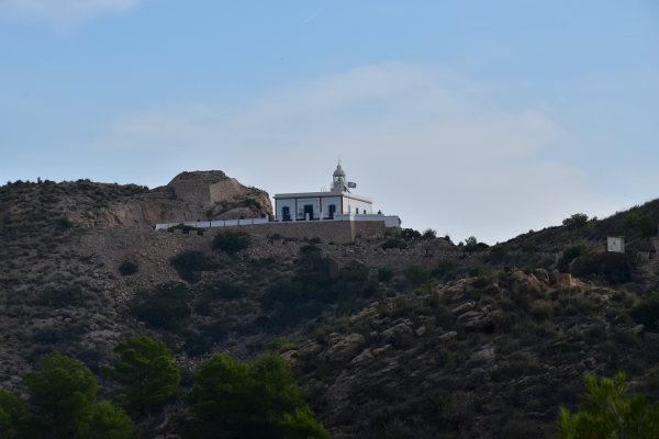 Een gebouw met toren, op een rots, bij de zee, vuurtoren Albir