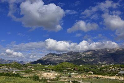 groen riet, groene bomen, het zandpad, met op de achtergrond een berg, blauwe lucht met witte wolken, achterland van Altea