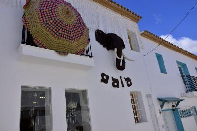 boutiek met mode, witte muren, parasol aan muur