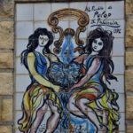 schilderij van tegels,twee vrouwen bij fontein